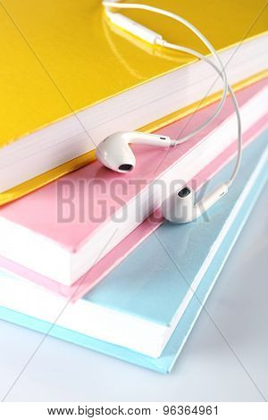 Earphones and books on table, closeup