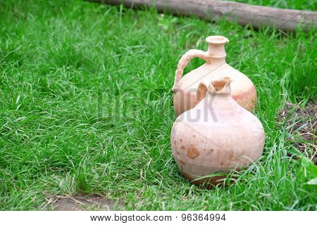 Old clay jugs on green grass background