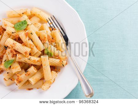 Plate of penne pasta with bread crumbs and basil.