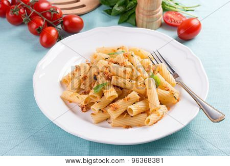 Plate of penne pasta with bread crumbs, basil and cherry tomatoes.