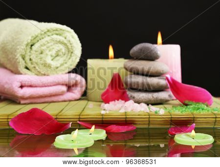 Spa still life with pink petals and candlelight on black background