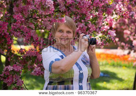 Happy adult woman photographer under pink flowering tree in garden