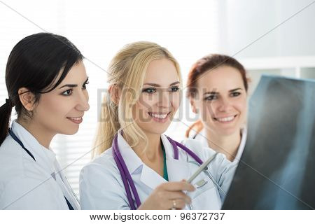 Portrait Of Three Smiling Female Medicine Doctors  Looking At X-ray Picture