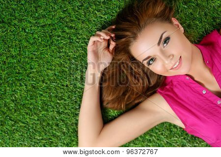 Young Beautiful Girl Laying On The Grass In Park