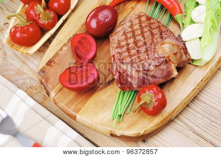 barbecued meat : beef ( lamb ) garnished with green lettuce and red chili hot pepper on wooden table with cutlery