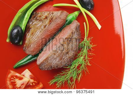 meat food : roast beef fillet mignon served on red plate with apples dill and tomatoes isolated over white background