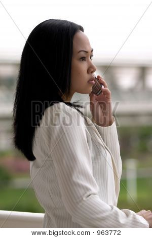 Asian Business Woman Looking Off With Cell Phone