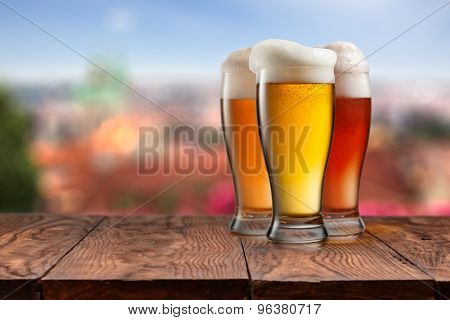 Three glasses of different beer on wooden table with summer in Prague on background. Natural bokeh
