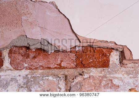 brick wall with missing and damaged plaster
