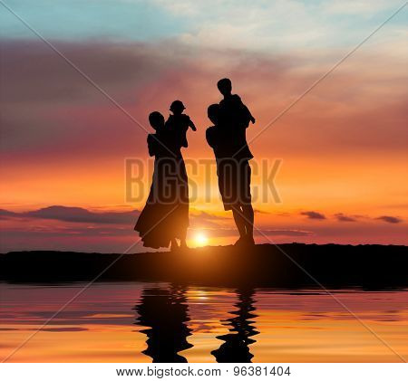 happy young family on a background of the magnificent sunset over the sea