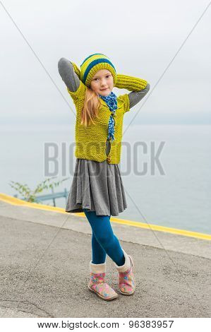 Cute little girl wearing green woolen pullover, hat and warm boots
