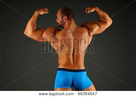 Muscular man shows his back
