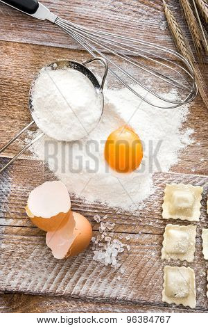 Egg in flour with other products on a wooden board