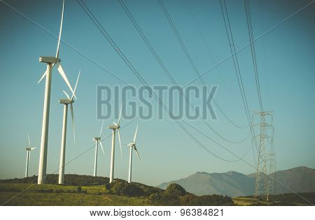 wind generator and high-voltage lines in a field on with blue sky and mountains on background