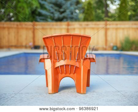 blue swimming pool and empty orange chair during summer
