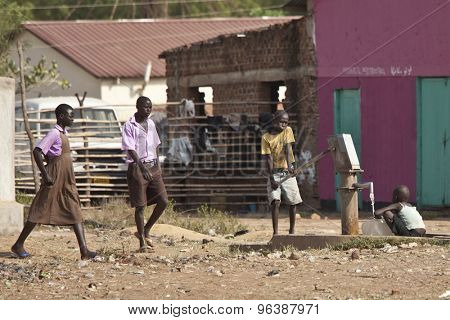 TORIT, SOUTH SUDAN-FEBRUARY 20, 2013: Unidentified students walk past two children at a a public water well in Torit, South Sudan
