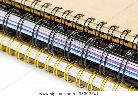 Three Closed Spiral Notebooks In A Pile.