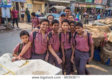 MUMBAI, INDIA - 16 JANUARY 2015: Schoolboys dressed in uniform gather around for a photograph in slum street.