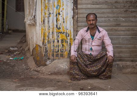 MUMBAI, INDIA - 12 JANUARY 2015: Indian man with mustache sits next to closed store in dirty empty street in brown patterned lungi and pink shirt.