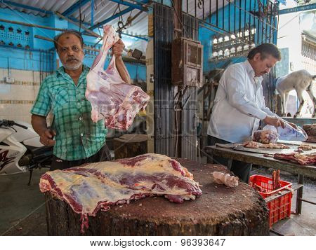MUMBAI, INDIA - 11 JANUARY 2015: Butcher shows piece of mutton while fellow worker packs meat next to him.