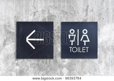 Unisex restroom or Toilet and arrow sign on concrete wall style boutique