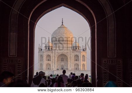 AGRA, INDIA - 28 FEBRUARY 2015: View of Taj Mahal from inside the Great Gate with visitors.