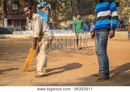 MUMBAI, INDIA - 16 JANUARY 2015: Adult Indian man holds wooden cricket bat and waits for ball while teammate, partly out of frame, stands next to him .