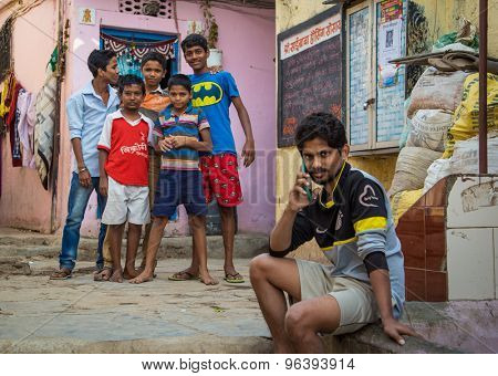 MUMBAI, INDIA - 16 JANUARY 2015: Five boys stand together in slum street while older boy talks on cellphone.