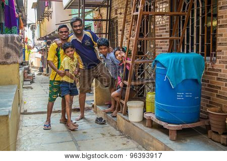MUMBAI, INDIA - 16 JANUARY 2015: Father and sons stand together in slum street.