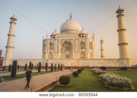 AGRA, INDIA - 28 FEBRUARY 2015: View of Taj Mahal towards South side. Visitor with camera. Post-processed with grain, texture and colour effect.