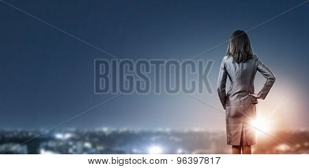 Rear view of businesswoman looking at night city