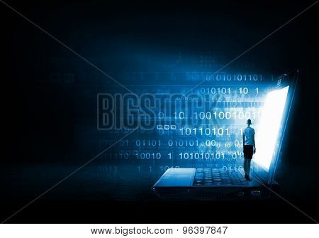 Rear view of businesswoman with suitcase standing on keyboard of big laptop