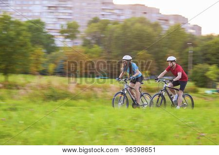 Cycling Concept: Young Caucasian Couple Having A Sppedy Bicycle Trip Outdoors. Blurred Motion Due To