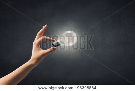 Close up of woman hand holding glass light bulb