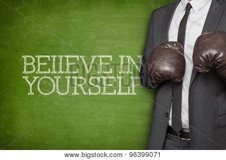 Believe in yourself on blackboard with businessman