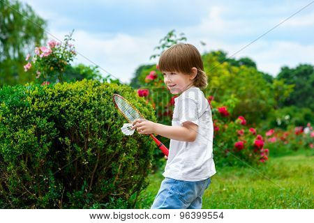 Portrait of happy little boy holding badminton racket and shuttlecock while standing on green grass