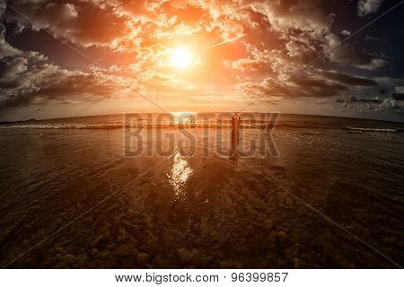 Inspirational Silhouette of a lone woman on a warm tropical beach sunset