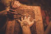 stock photo of haldi  - Drawing process of henna menhdi ornament on woman - JPG