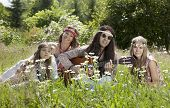 image of hippy  - Hippie family sitting in the field and playing guitar on a sunny summer day - JPG