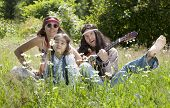 picture of hippy  - Hippie family playing guitar in the field on a sunny summer day - JPG