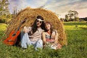 foto of hippy  - Hippie couple on the haystack in the midst of rural meadow - JPG