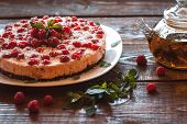 foto of teapot  - Appetizing vegetarian pie from protein jelly with fresh berries of raspberry and a teapot with green tea - JPG