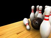 foto of bowling ball  - Ten Pin Bowling Scene with Bowling Ball and Bowling Pins on a Bowling Lane with Black Background - JPG