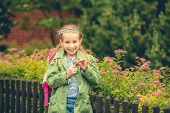 picture of schoolgirls  - little cute schoolgirl with a school backpack on the background of flowers on the street - JPG