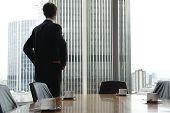 stock photo of premises  - Single adult business man waiting for meeting to begin in Board room - JPG