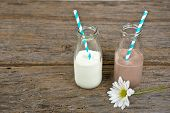stock photo of white-milk  - Chocolate and white milk with striped straws in retro glass milk bottles and daisy on rustic wood - JPG
