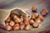 picture of hazelnut  - A bag of hazelnuts on vintage wooden table closeup with shallow depth of field