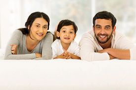 pic of indian  - portrait of beautiful young indian family relaxing on bed - JPG