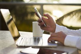 stock photo of cell  - businessman in the morning with a cell phone laptop and coffee - JPG