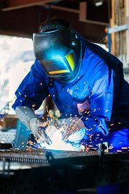 stock photo of welding  - Welder bonding metal with welding device in workshop - JPG